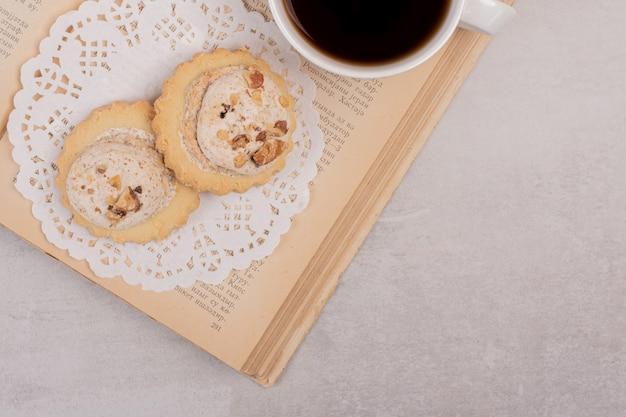Biscotti di farina d'avena e tazza di tè sul libro aperto.