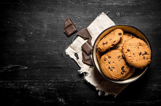 チョコレートのかけらが入ったボウルにオートミールクッキー。黒い木製のテーブルの上。