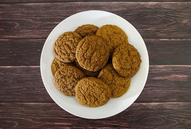 나무 테이블에 접시에 오트밀 쿠키 위에서보기