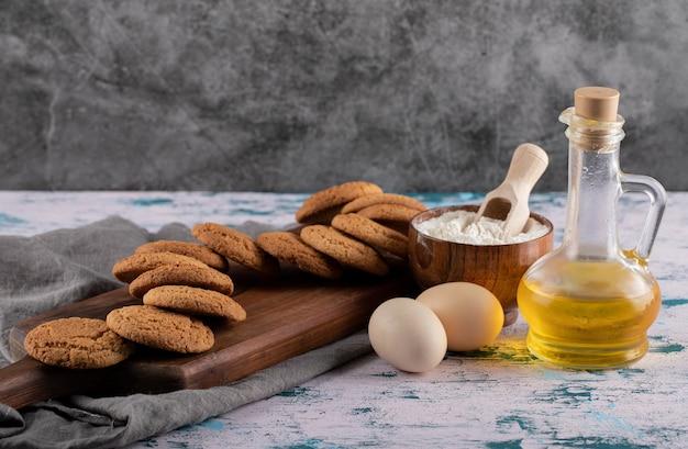 Овсяное печенье на деревянном блюде с ингредиентами вокруг.