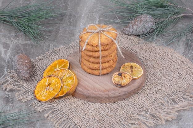 ドライオレンジスライスが周りにある木製の大皿にオートミールクッキー