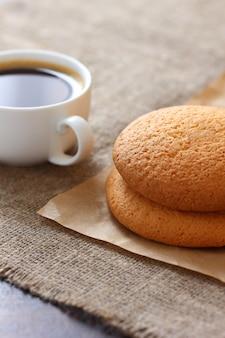 クラフト紙上のオートミールクッキー、黄麻布、テーブルクロスにコーヒーと白いマグカップ