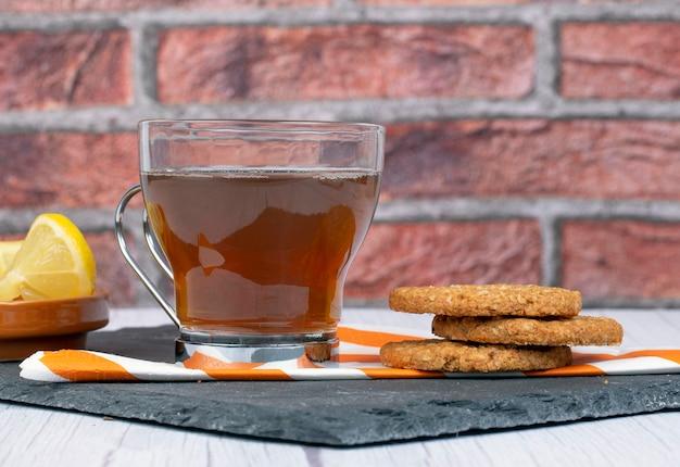 ナプキンと長方形の石のプレートにオートミールクッキーとお茶とレモンスライスの受け皿が付いています