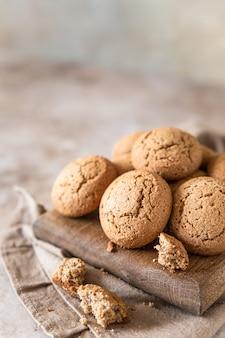 나무 커팅 보드 갈색 콘크리트 배경에 오트밀 쿠키 건강한 간식 또는 디저트