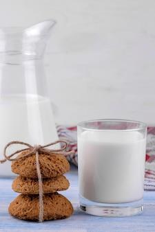 オートミールクッキーが前景のスタックに積み上げられ、ミルクが青い木製のテーブルのグラスに積み上げられました。焼く。うまい。