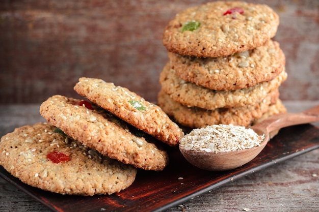 Oatmeal cookies and a spoon with oat flakes on a wooden table