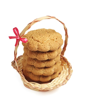 Oatmeal cookies in wicker basket on a white background