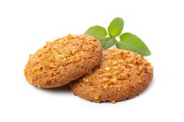白い背景に緑のミントの葉とオートミールクッキー。ダイエット食品。