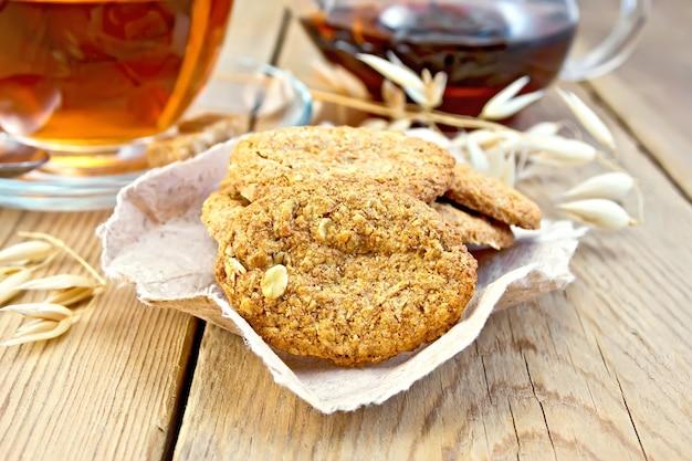 종이에 귀리 줄기가 있는 오트밀 쿠키, 차 한 잔, 찻주전자 나무 판자 배경