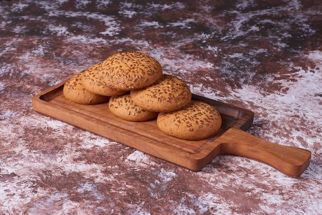 ビー玉を横切る木製の大皿に黒いクミンが入ったオートミールクッキー。