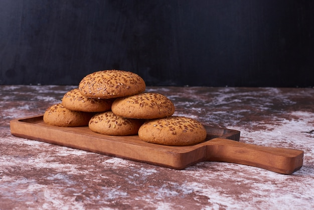 Oatmeal cookies with black cumin on a wooden platter across the marble.