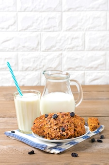 Oatmeal cookies with cereal and raisins , milk in bottle and in glass on wooden background, healthy snack.