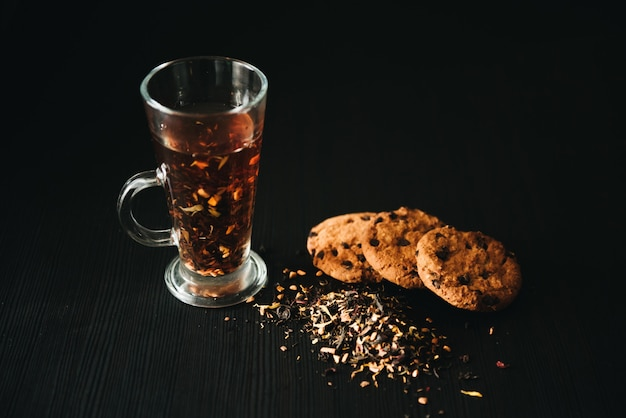 Oatmeal cookies with chocolate chips. cookies with a cup of tea on a black wall