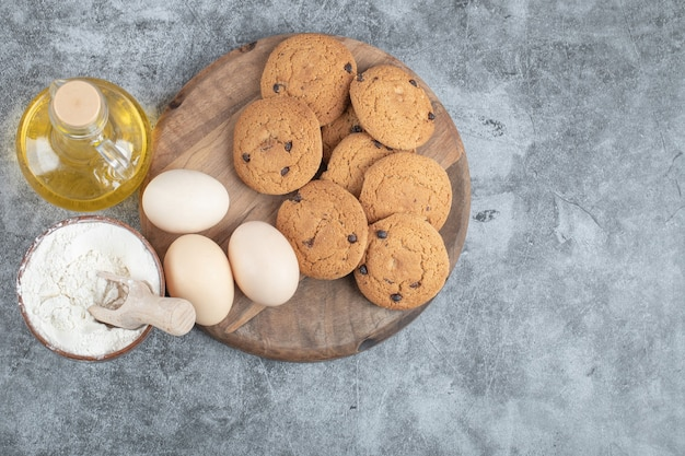 Oatmeal cookies with chocolate drops on a wooden board with ingredients around