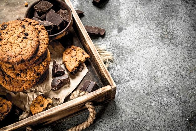 ボウルにチョコレートが入ったオートミールクッキー。素朴な背景に。
