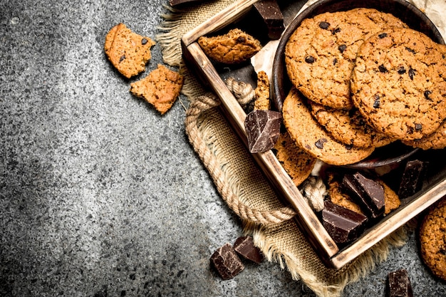 Овсяное печенье с шоколадом в миске на деревенском фоне