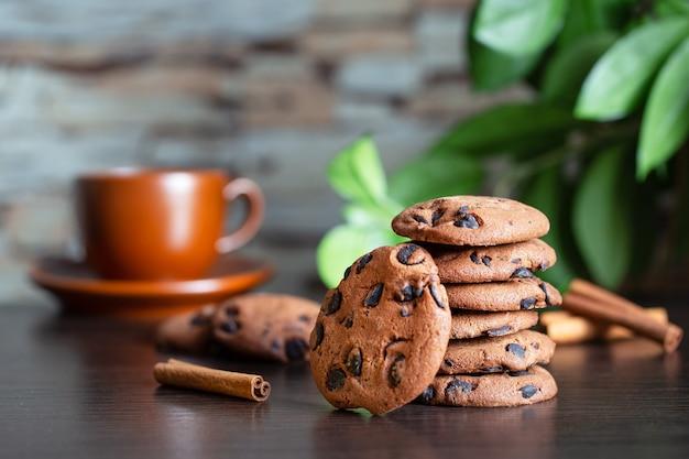 一杯のコーヒーと緑の葉を背景にテーブルにチョコレートとオートミールクッキー。朝食または朝のコーヒーのコンセプト