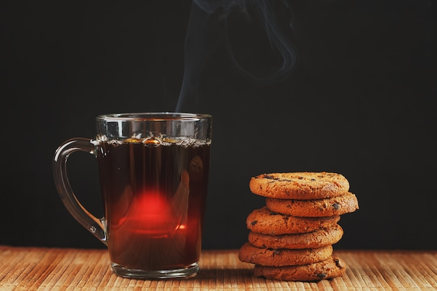 Oatmeal cookies with chocolate pieces and a mug of aromatic black tea