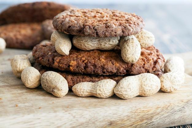 Овсяное печенье с измельченным арахисом лежит телом арахиса в скорлупе на столе