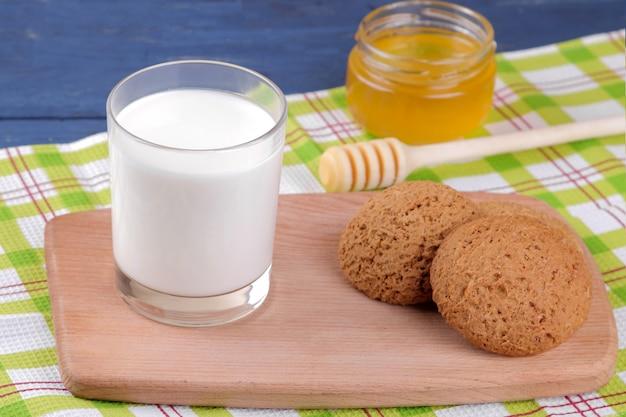 青い木製のテーブルの上のボードにミルクと蜂蜜とオートミールクッキー