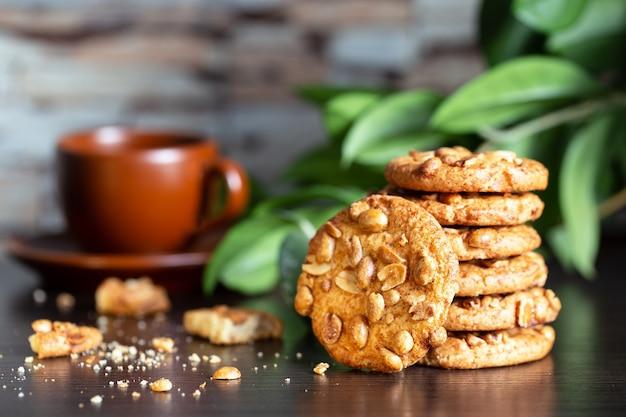 緑の葉の背景にコーヒーのカップとテーブルの上のナッツとオートミールクッキー