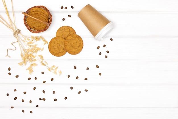 Овсяное печенье с ушками стеблей овса, чашкой кофе и кофейными зернами. полезный кофейный десерт на вынос