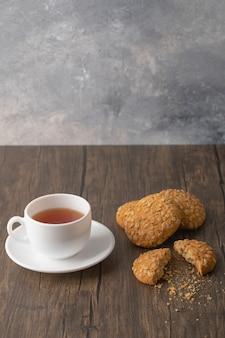 Biscotti di farina d'avena con semi e cereali vicino a una tazza bianca di tè nero