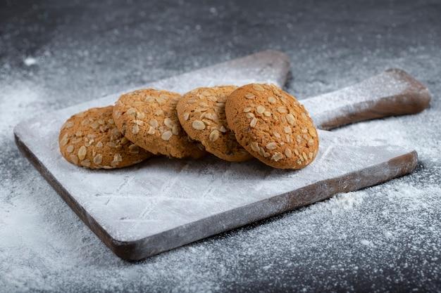 검정색 배경에 설탕 가루와 오트밀 쿠키.