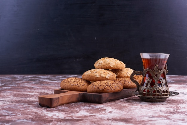 Oatmeal cookies on a wooden platter with a glass of tea .