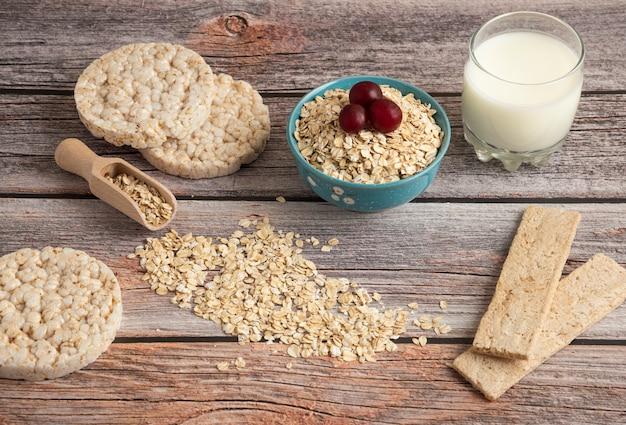 オートミールクラッカー、ベリーと穀物とテーブルの上のミルクのカップ