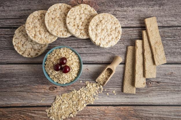 Cracker di farina d'avena, cereali con frutti di bosco e una tazza di latte sul tavolo, vista dall'alto