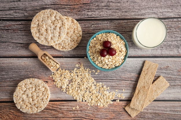 Oatmeal crackers, grains with berries and a cup of milk on the table, top view
