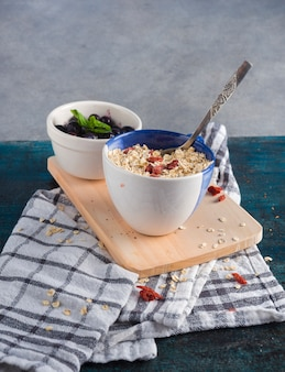 Oatmeal in cup with berries on wooden board