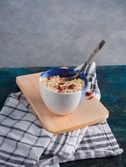 Oatmeal in cup on wooden board