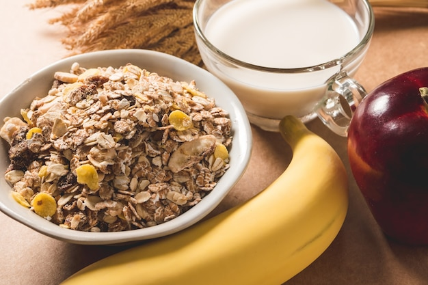 Oatmeal flakes in a bowl, milk, apple and banana on wooden table. healthy breakfast concept.