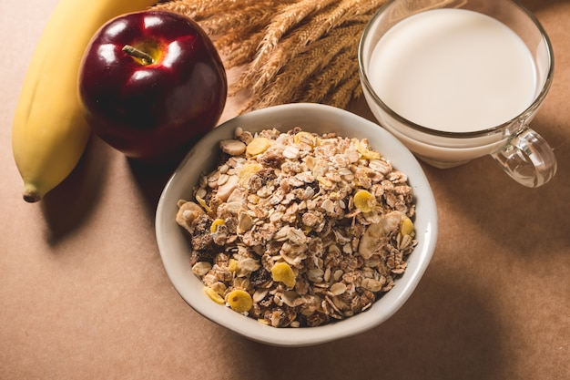 Oatmeal flakes in a bowl, milk, apple and banana on wooden table.