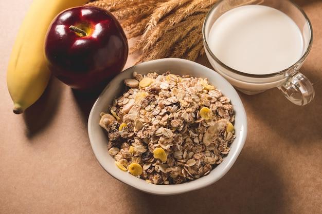 그릇, 우유, 사과 나무 테이블에 바나나에 오트밀 조각.