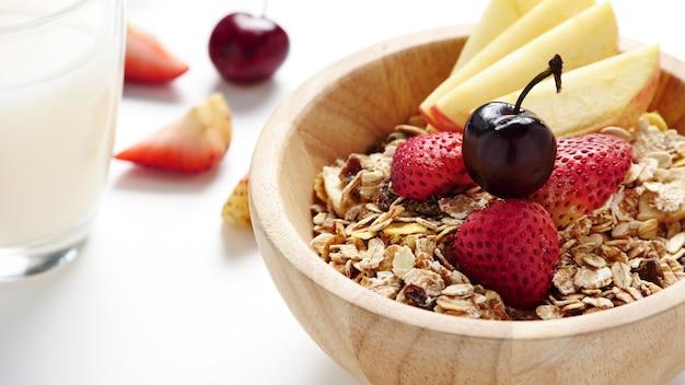 Oatmeal flakes, milk, and fresh fruits on white background.