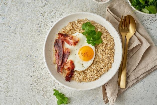 Овсянка, жареное яйцо, жареный бекон. сбалансированная еда. интуитивно понятная еда, вид сверху, копия пространства