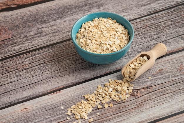 Зерна овсянки в пластиковой миске на столе