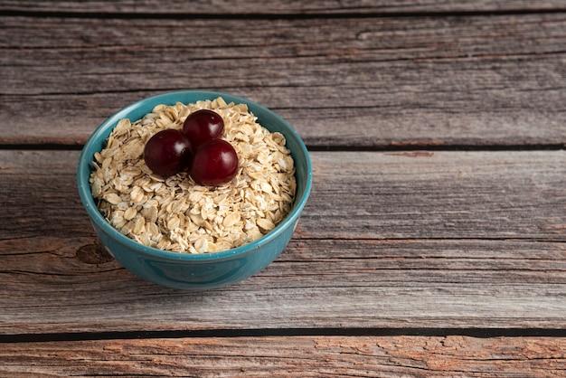素朴なボウルに果実とオートミールの穀物