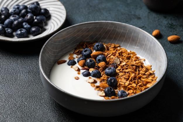 ブルーベリー入りオートミールグラノーラ。ドライブレックファースト。健康食品やダイエットの概念。スペースをコピーします。ギリシャヨーグルトとグラノーラ。アーモンドとベリーのグラノーラ。健康的な栄養。ベリーとミューズリー。