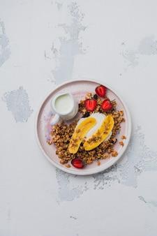 明るい背景に白いセラミックプレートにヨーグルト、新鮮なイチゴとバナナ、チアシード、ヒマワリと蜂蜜とオートミールグラノーラ。上面図。