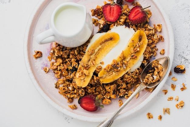 明るい表面に白いセラミックプレートにヨーグルト、新鮮なイチゴとバナナ、チアシード、ヒマワリと蜂蜜とオートミールグラノーラ