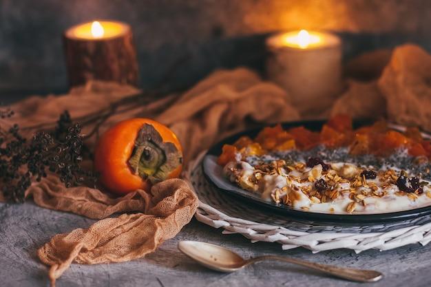 オートミールグラノーラ、ヨーグルト、ドライフルーツ、種子、蜂蜜、柿のボウル