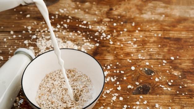 그릇에 오트밀입니다. 우유가 나무 배경에 있는 그릇에 붓고 있습니다. 건강한 아침 식사