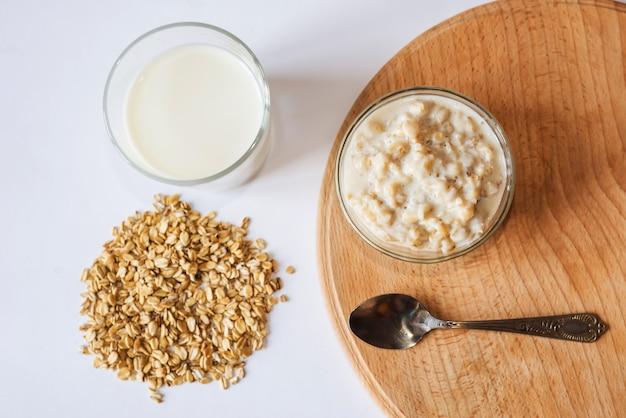 나무 보드에 우유, 숟가락 및 오트밀 한 잔과 함께 그릇에 오트밀. 위에서 봅니다.
