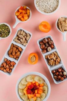 Овсянка в миске с фруктами, орехами, арахисовым маслом, овсяными хлопьями