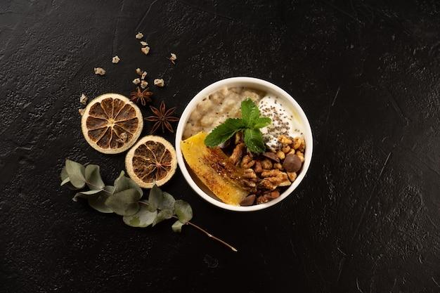 ミントの葉とチョコレートドロップで飾られた、ヨーグルト、チアシード、バナナ、クルミが入った丸い白いプレートのオートミール。健康的な菜食主義の食事