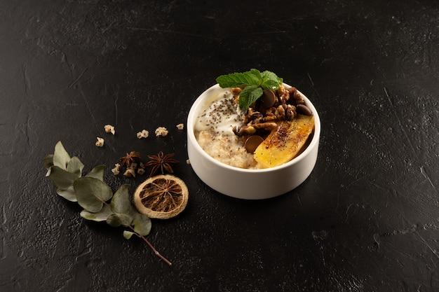 민트 잎과 초콜릿 방울로 장식 된 요구르트, 치아 시드, 바나나, 호두가 들어간 둥근 흰색 접시에 담긴 오트밀. 건강한 채식 식사